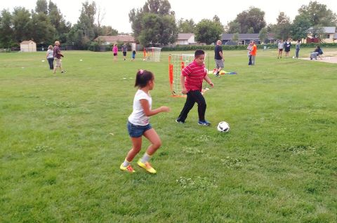 Sherlyn Ortiz (left front) attempts to steal the ball from her brother, Juan Ortiz, during the weekly SeSSI Kick-Around at Evans International Elementary School in Falcon School District 49. Their mother, Claudia Rivera, said her children have enjoyed having a similar interest in soccer. Photo by Lindsey Harrison